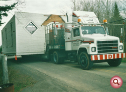 A building being moved by truck.